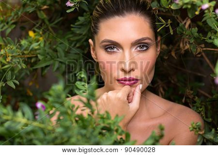 attractive female beauty behind the bush