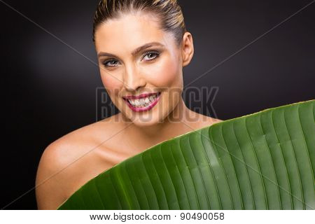 happy young woman standing behind green leaf over black background