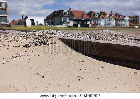 A Groin On The Beach With Houses In Background