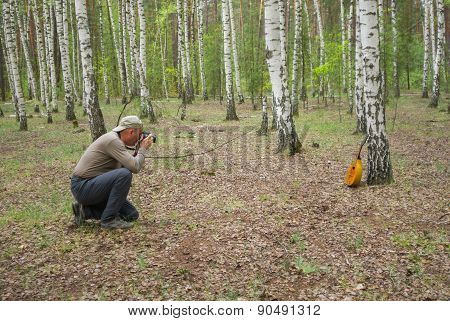 Mature photographer making an outdoor photo of mandolin