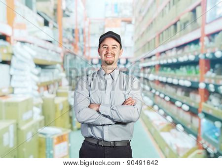 smiling worker crossed arms in warehouse