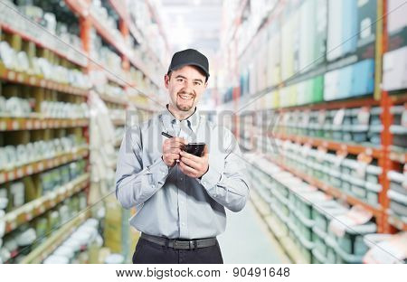 smiling worker with tablet in warehouse