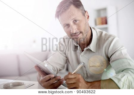 Man reading news on both paper and digital tablet