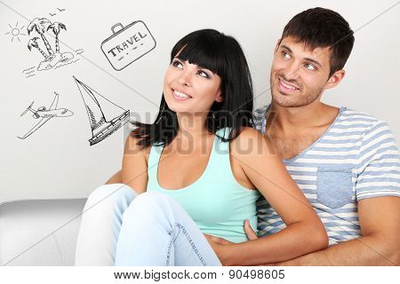 Dreaming concept. Beautiful loving couple sitting on sofa in room on grey background