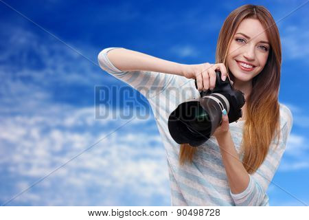 Young female photographer taking photos on blue sky background