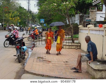 boys-monks walking under an umbrella on the streets of Laos
