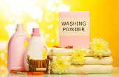 foto of detergent  - Detergent with washing powder and towels on yellow background - JPG