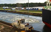 foto of locomotive  - A locomotive with the guide lines attached leads a large ship through the Panama Canal - JPG