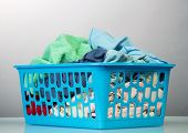 image of dirty-laundry  - Blue basket with dirty laundry isolated on white - JPG