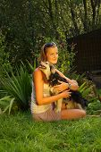 stock photo of stray dog  - A young beautiful woman with blonde hair is holding lovingly a stray dog in her arms in a backyard garden with green grass - JPG