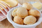 stock photo of brazilian food  - Brazilian snack pao de queijo (cheese bread) on white plate with cheese ham butter on wooden table. Selective focus ** Note: Shallow depth of field - JPG