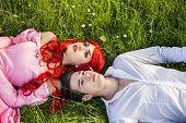 stock photo of encounter  - Romantic Fairy Tale Couple Sitting in Garden among Flowers in Peaceful Idyllic Setting - JPG