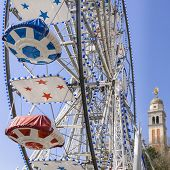 picture of ferris-wheel  - Ferris Wheel at the county fair with the sky in the background and a bell tower - JPG