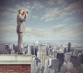 picture of binoculars  - Curious businessman looks beyond with his binoculars - JPG