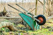 picture of wheelbarrow  - Turned over wheelbarrow resting against mesh fence bottom up - JPG