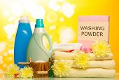 picture of detergent  - Detergent with washing powder and towels in basket isolated on yellow background - JPG