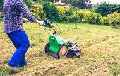 stock photo of grass-cutter  - Closeup of man with straw hat and plaid shirt mowing lawn with a lawnmower machine - JPG