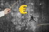 stock photo of rod  - Man jumping for 3D golden euro symbol bait on fishing rod hand holding with old mottled concrete wall background - JPG