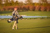 pic of golf bag  - Male golf player carrying bag on fairway during sunset - JPG