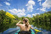pic of kayak  - Woman kayaking along a beautiful tropical jungle river - JPG