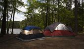 picture of nylons  - Two nylon tents in a campsite next to a lake surrounded by forest - JPG