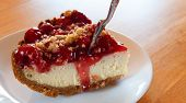 picture of cheesecake  - Cheesecake with cherry topping and it has a fork going in - JPG