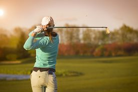 picture of swing  - Close up of female golf player swinging golf club on fairway during sunset - JPG