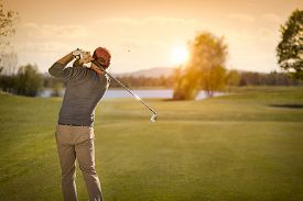 stock photo of swing  - Male golf player swinging club at beautiful sunset in background - JPG