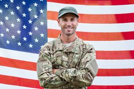 stock photo of army soldier  - American soldier holding recruitment sign against american flag - JPG
