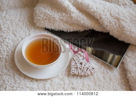 Cup Of Tea And Tablet Over White Textile Background