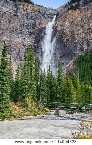 Small footbridge across the turbulent river.  Waterfall Takakkaw in Yoho National Park in the Rocky Mountains