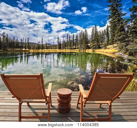 Adorable lake. Two wooden deckchairs for tourists. Coniferous forest is reflected in the mirrored water of lake. Warm autumn day in Jasper National Park in the Rocky Mountains
