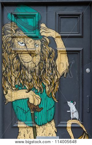 April 2014 - Bristol, United Kingdom: A Graffiti On A Black Door Of A Lion With A Green Hat On