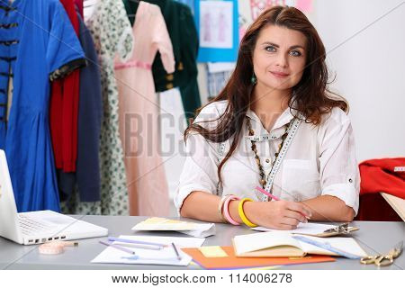 Smiling Female Fashion Designer Holding Drawing Pad And Pencil Making Sketch