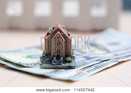 Many Dollar Banknotes And A House Model; Concept Of Buying A House
