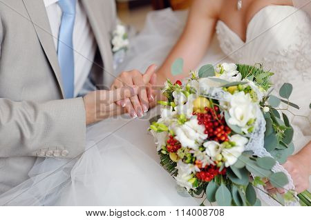 Hands With Rings Bride And Groom On The Background Of A Wedding Bouquet