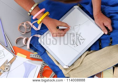 Female Fashion Designer Hands Holding Drawing Pad And Pen Making Sketch