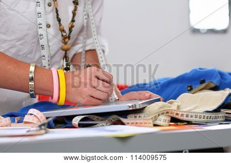 Female Fashion Designer Hands Holding Drawing Pad And Pen