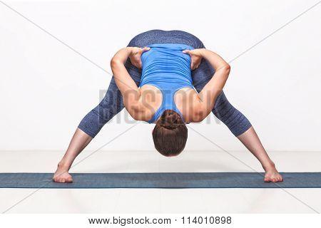 Beautiful sporty fit woman practices Ashtanga Vinyasa yoga asana Prasarita padottanasana B - wide legged forward bend B