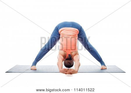 Beautiful sporty fit woman practices Ashtanga Vinyasa yoga asana Prasarita padottanasana C - wide legged forward bend C isolated on white background