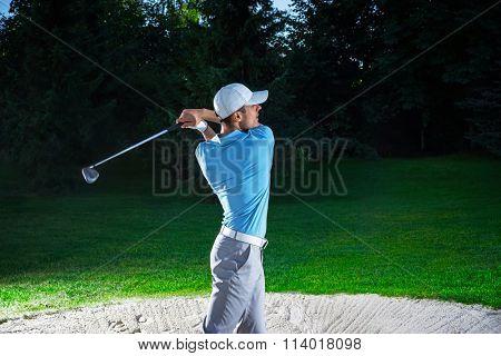 Golfer with club on a lawn