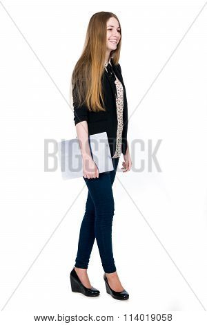 Full Length Of Young Blond Smiling Girl Holding Clipboard Looking Aside.