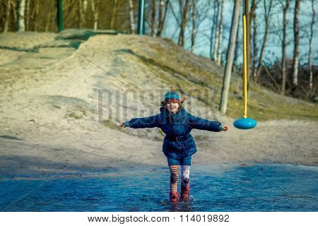 Girl running and jumping in the deep puddle at the autumn playground