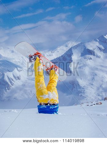 Legs of a snowboarder stuck in deep snow upside down, mountains at the background