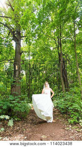Bride waving dress in a forest