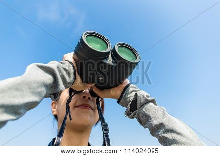 Woman use of the binoculars with clear blue sky