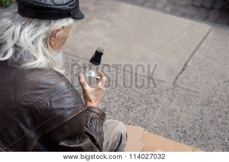 Portrait of a poor senior man sitting on cardboard with a bottle of whiskey. Old drunk man with white beard. Close up of homeless sitting on cardboard in a drunken state and drinking whiskey.