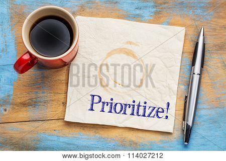 prioritize - reminder or productivity concept on a napkin with a cup of coffee