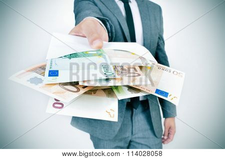 a young caucasian man wearing a gray suit gives an envelope full of euro bills to the observer