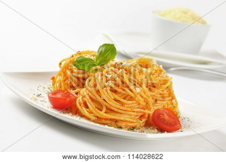 close up of cooked spaghetti with red pesto and grated parmesan cheese on white plate
